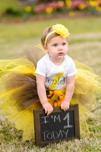 children's photography little blonde girl holding sign for one year photography session