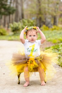blonde haired one year old girl sitting in green chair with yellow tutu and flowered headband
