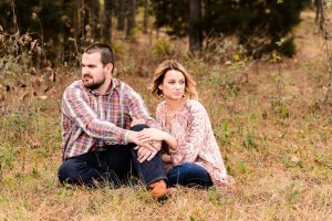 couple sitting in field for engagement session in middle georgia