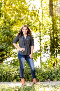 brown haired girl wearing blud jeans and gray shirt standing and laughing for senior portrait session in middle georgia