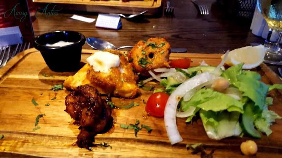 Mixed starter on a wooden board. Fish pakora, tandori chicken and  grilled prawns.