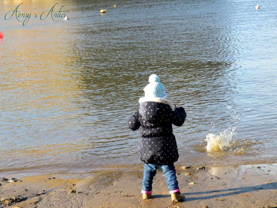 Little girl throwing pebbles into the sea