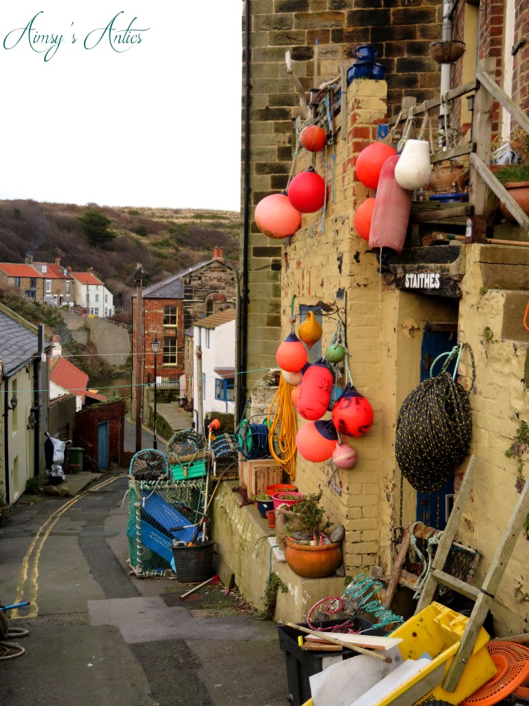 Street with fishing equipment on the walls in Staithes