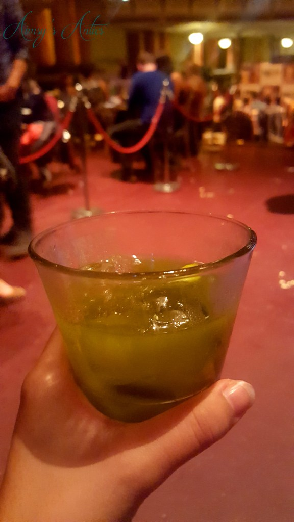 Image of Green coloured cocktail being held in a hand
