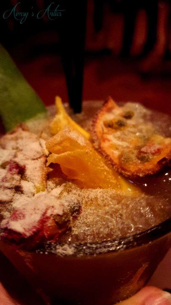Cocktail with passionfruit, orange and rose decoration, dusted with icing