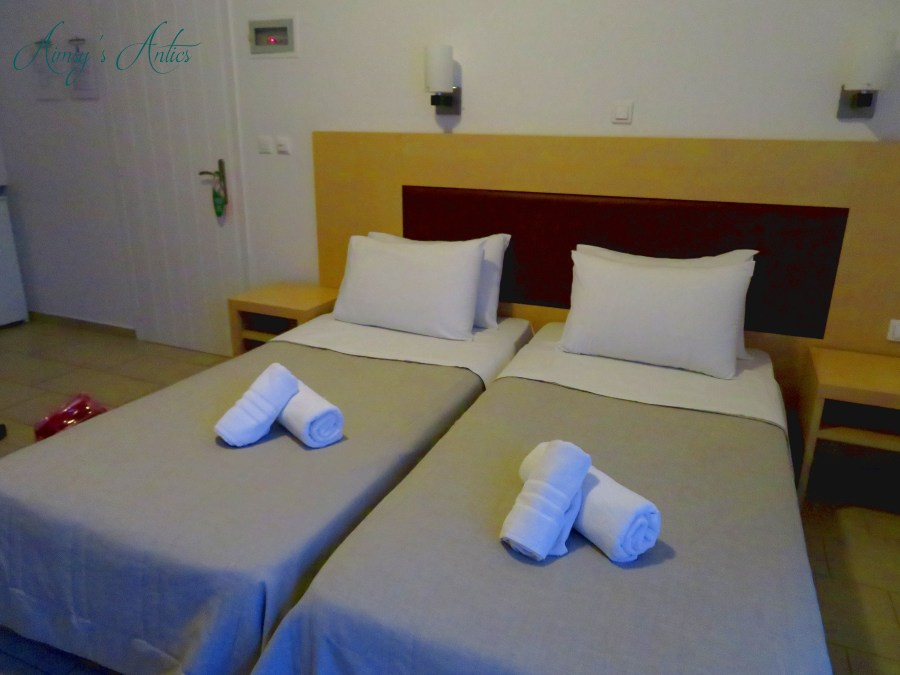 Image of Anna Maria hotel room in Mykonos. Two twin beds with folded towels on them.