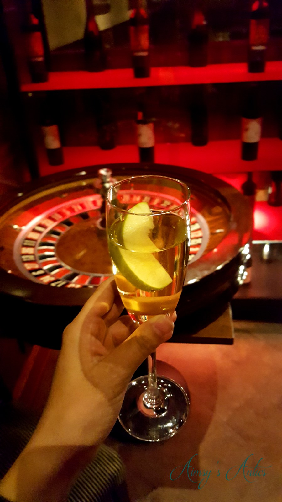 hand holding a champagne flute with a cider and gin cocktail in fruit of a roulette wheel