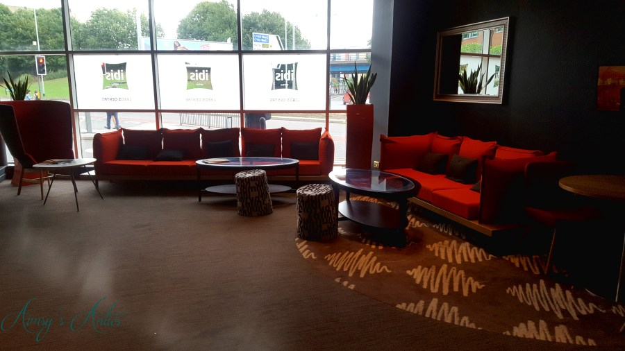 Image of red sofas in the reception area of Ibis hotel Leeds
