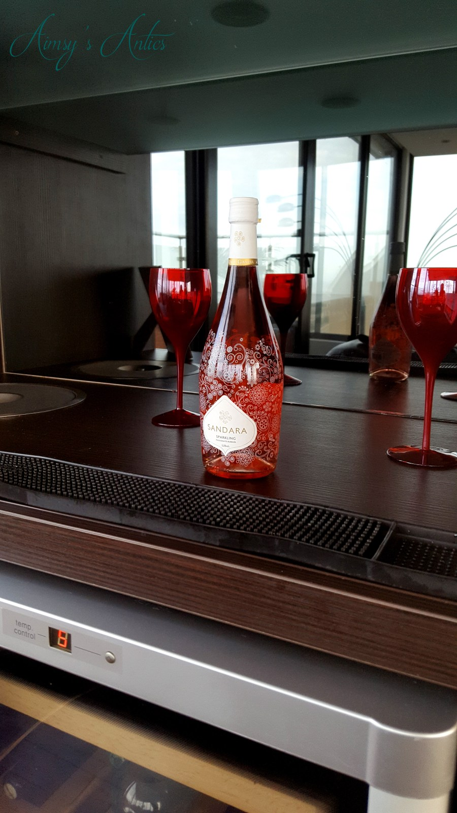 Image of the bar area in the High-end Beachside house with red wine glasses and a bottle of pink fizz