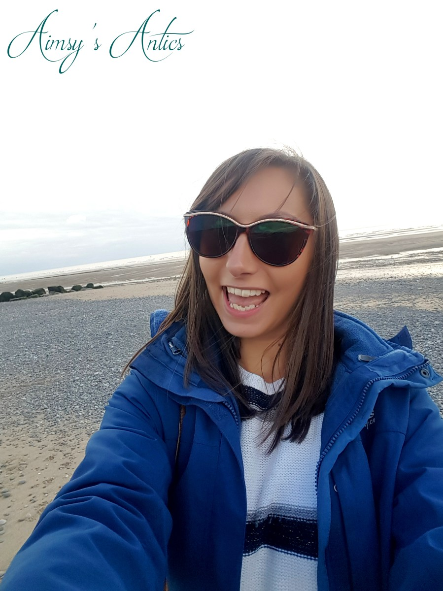 Image of a selfie of a woman on the bach at Cleveleys, smiling and wearing sunglasses.