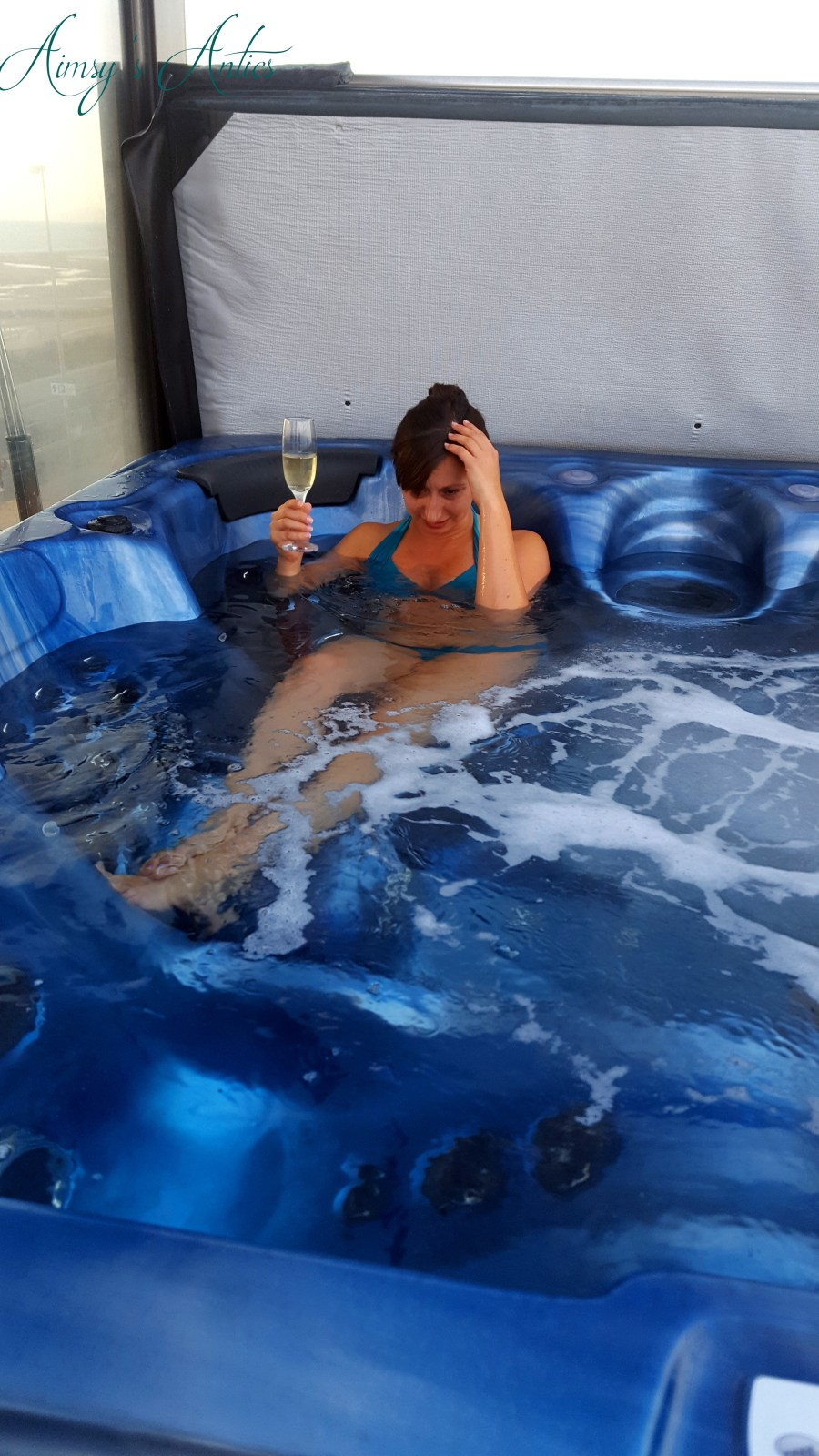 Image of a woman in the hottub with a glass of prosecco in hand at the High-end beachside house