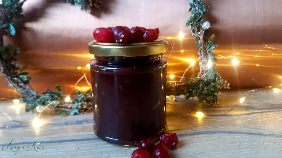 Image of a jar of Cranberry and red Onion relish, with cranberries decorating the jar, a heart Christmas wreath and fairy lights in the background. All against a copper backdrop