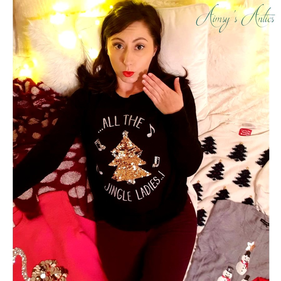 Image of a girl posing with a shocked face, surrounded by various Christmas Jumpers. Fairy lights in the background.