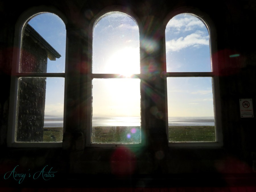 View out of three windows in the Grange-over-Sands train station, with the sun shining through the middle window.