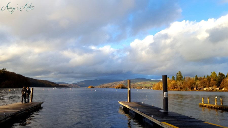 Lake Windermere in Bowness-on-Windermere with a view of two jetties and hill sin the distance.