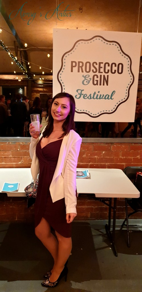 Woman holding a drink of rhubarb and custard gin with lemonade in front of the prosecco and gin festival wall sign.