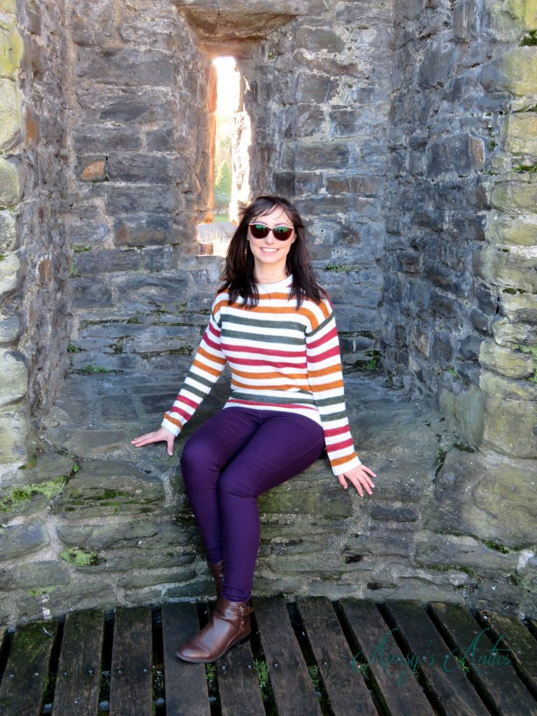 Woman sat on the town walls of Conwy is a striped jumper and purple jeans