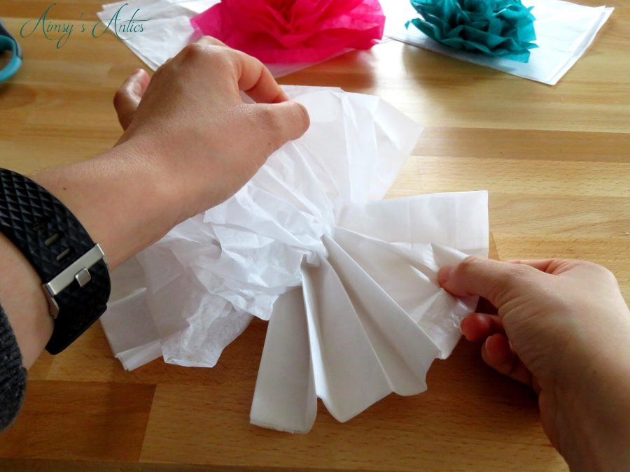 Hands unfolding white tissue paper into the shape of a flower