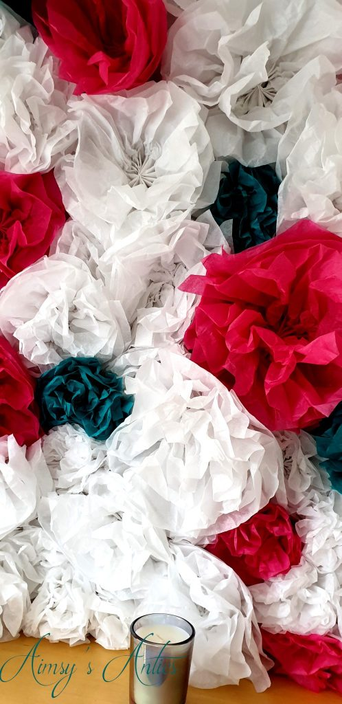 Close up shot of tissue paper flower wall, with a small candle in front of it.