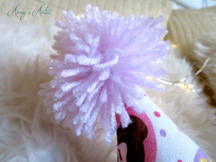 Glittery pale pink pom-pom clos up shot on top of one of the crown points on the cushion.