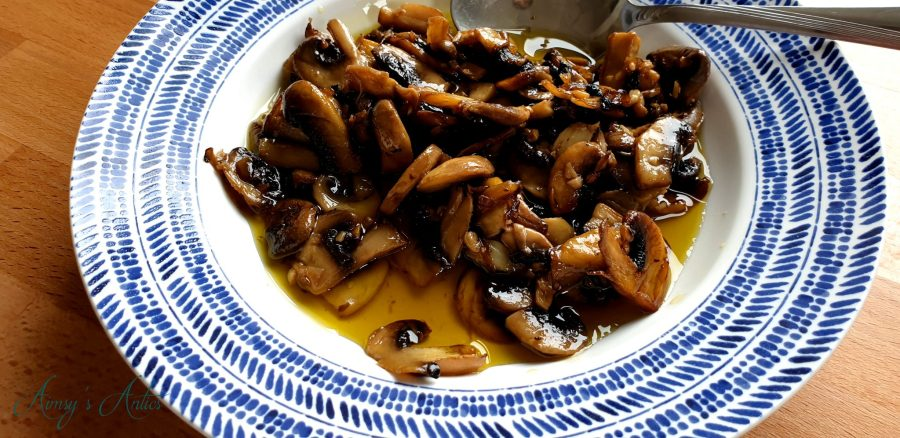 Garlic mushrooms served in a blue and white bowl with a spoon.