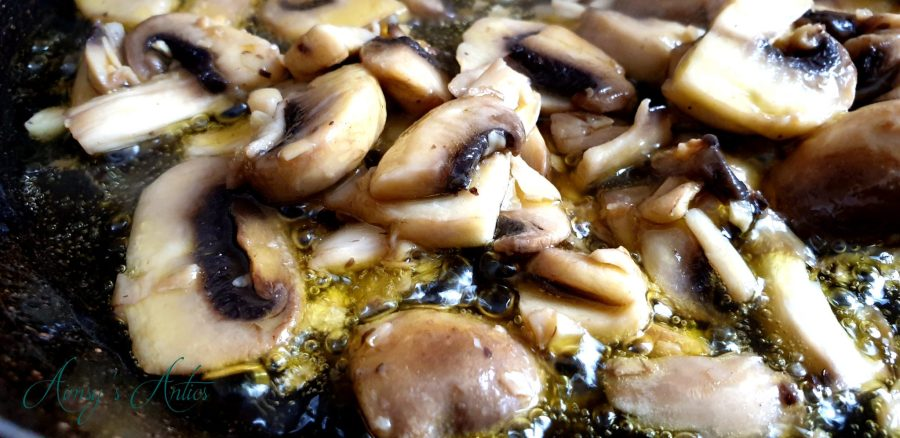 Mushrooms frying in a pan with garlic., oil is bubbling