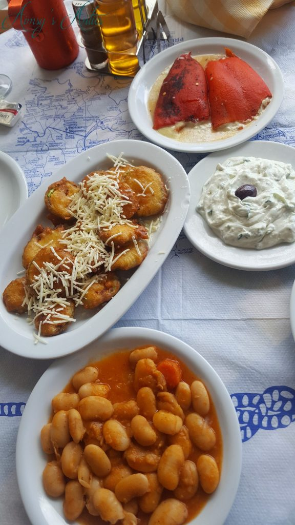 A selection of Greek Meze, including giant beans, Pepper stuffed with cheese, courgette fritters and tzatziki.