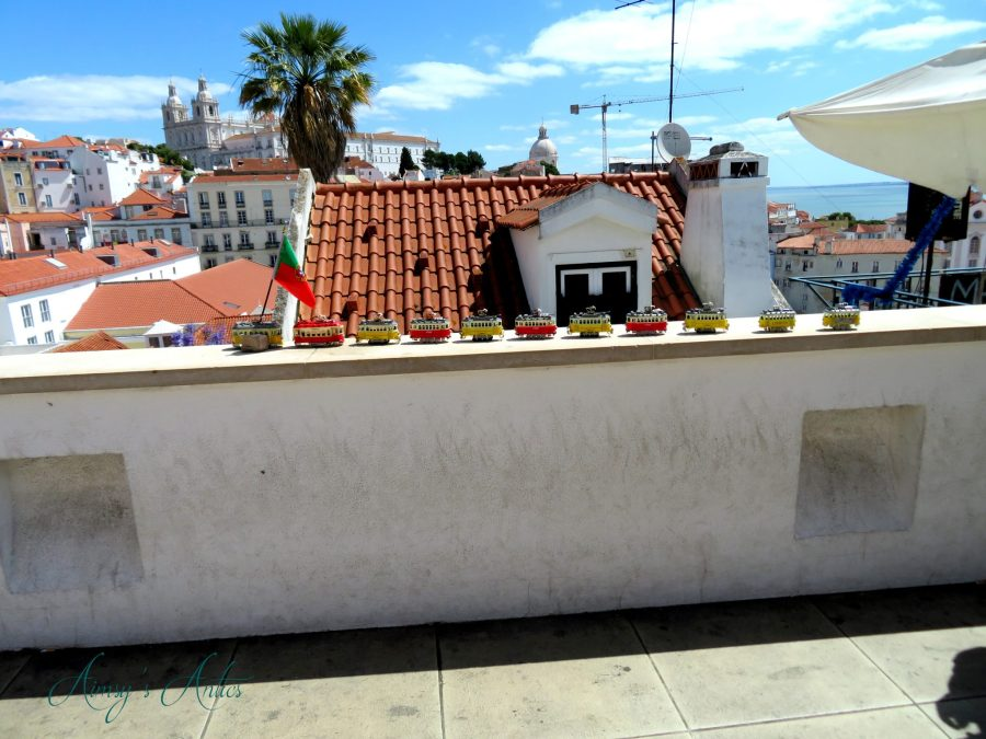 Tram toys lined up on a wall at Miradouro das Portas do Sol Viewpoint
