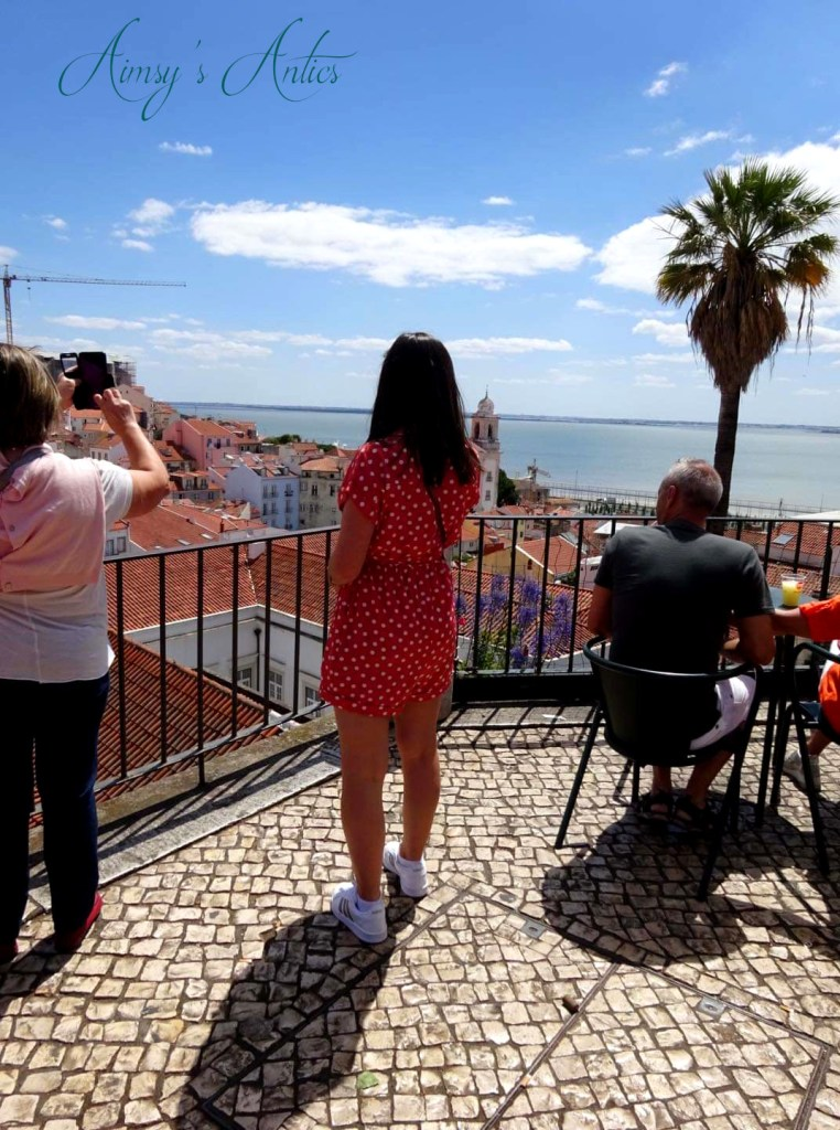 Woman looking out at the view from Miradouro das Portas do Sol Viewpoint