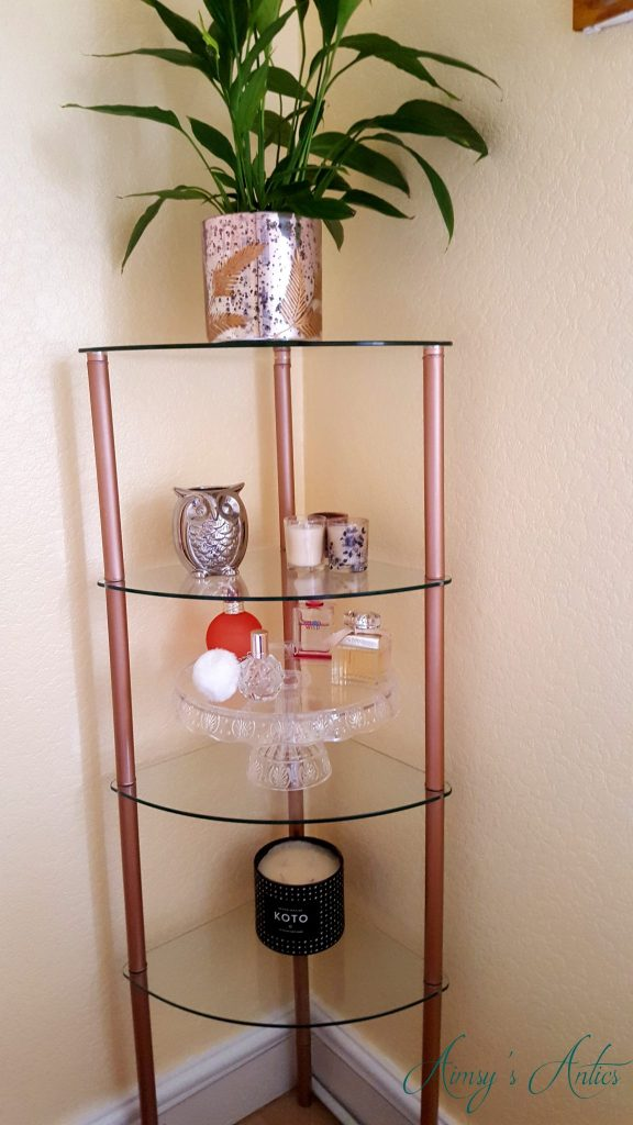 Up Styled curved glass shelving unit with decorations placed ont he shelves