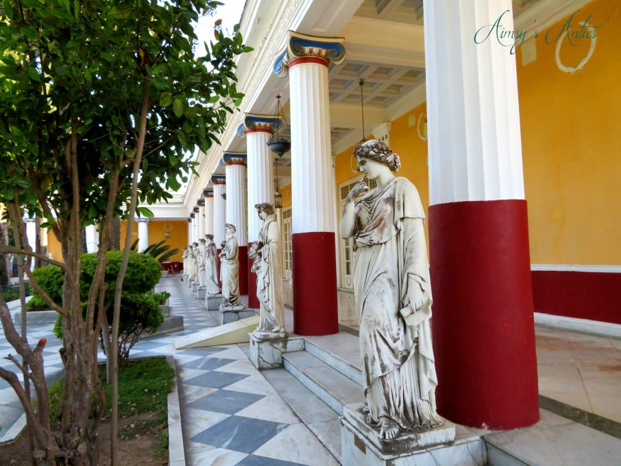 Terrace area in Achilleion Palace, with several marble statues and pillars