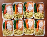 Pan-Roasted Salmon with Italian Noodles and Baby Vegetables, individually plated and ready for transport to Palm Springs.