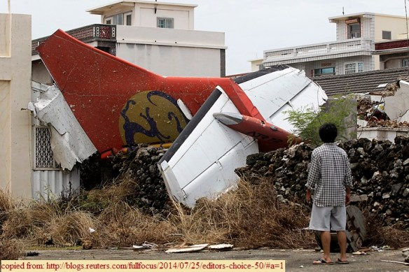 A man looks at the wreckage of a TransAsia Airways turboprop plane that crashed on Penghu island