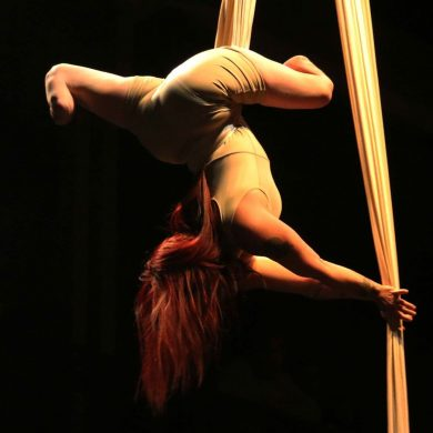 Bilateral amputee Erin Ball suspends elegantly upside down on aerial fabric.