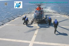 "Los ""camisas azules"" a punto de ""trincar"" (amarrar) los esquies del helicóptero a la cubierta del buque./The ship's crew about to secure the helicopter's skies to the deck of the ""Artigas""."