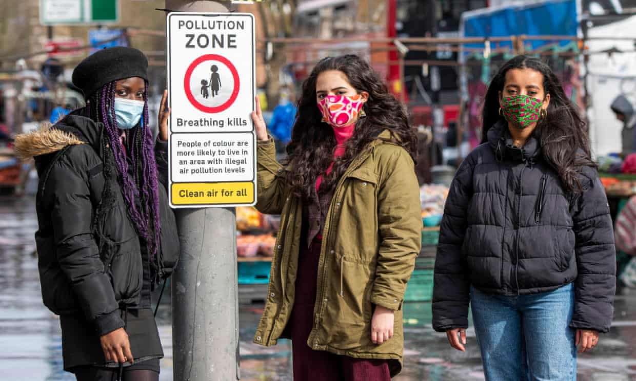 Three members of Choked Up with a road signs that states 'pollution zone, breathing kills'