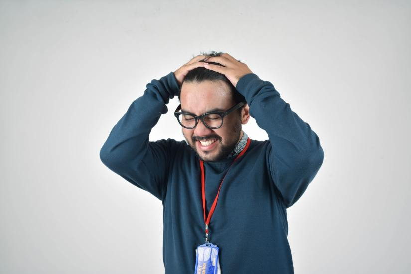 Man in blue sweater expressing frustration