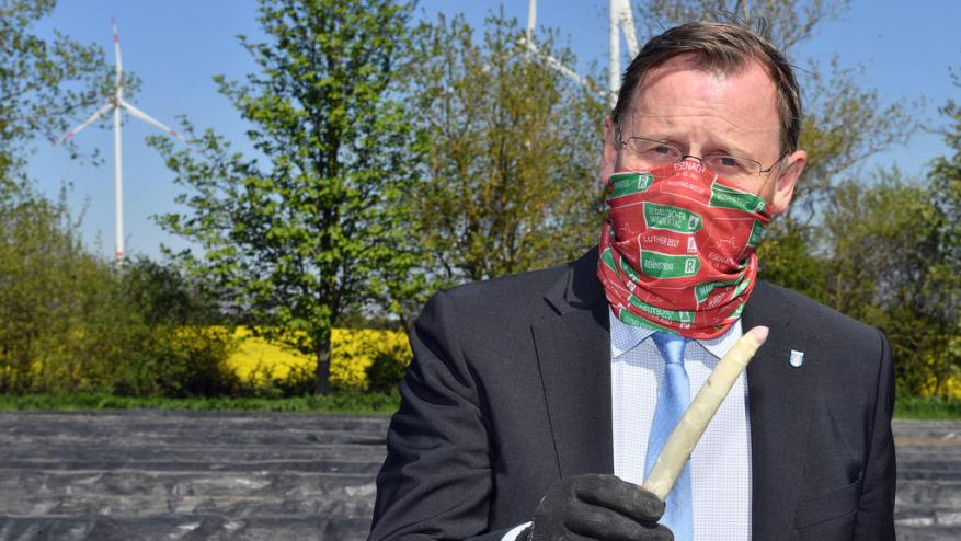 April 22, 2020, Thuringia, Kutzleben: Bodo Ramelow (Die Linke), Prime Minister of Thuringia, presents an asparagus spear in a field of the Spargelhof Kutzleben. The company in the Unstrut-Hainich district is one of the largest asparagus growers in Thuringia