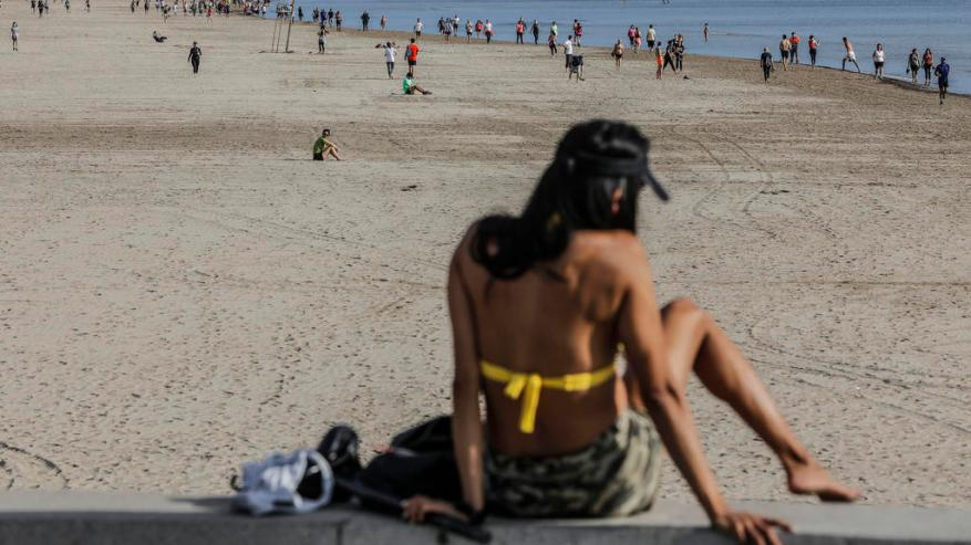 May 02, 2020, Spain, Valencia (Comunidad Valenciana): A woman sits in her bikini on the beach in Malvarrosa. From this weekend, citizens in Spain, which was badly affected by the corona pandemic, will be allowed to go outside again for the first time in seven weeks