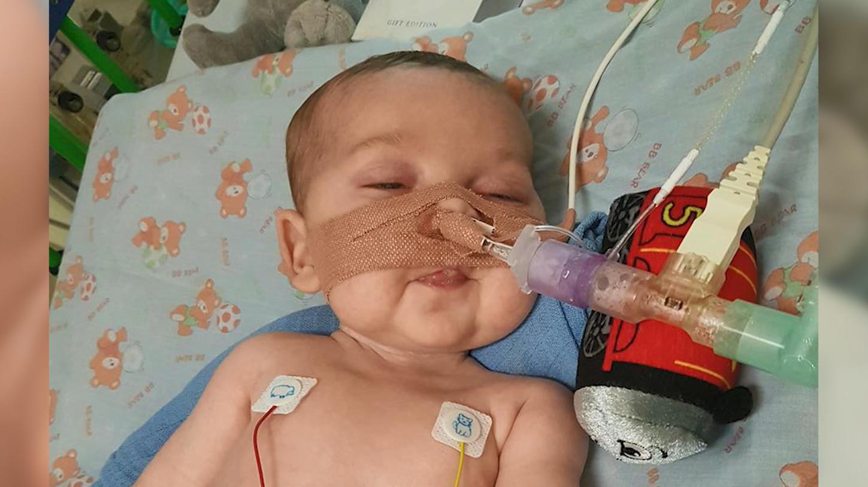 Baby Charlie liegt an Schläuchen angeschlossen im Krankenhausbett.