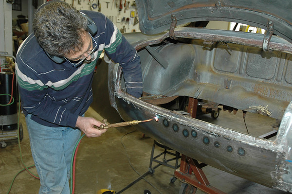 Carlos is adjusting the lower valance I made with the English wheel to fit the vehicle contour.