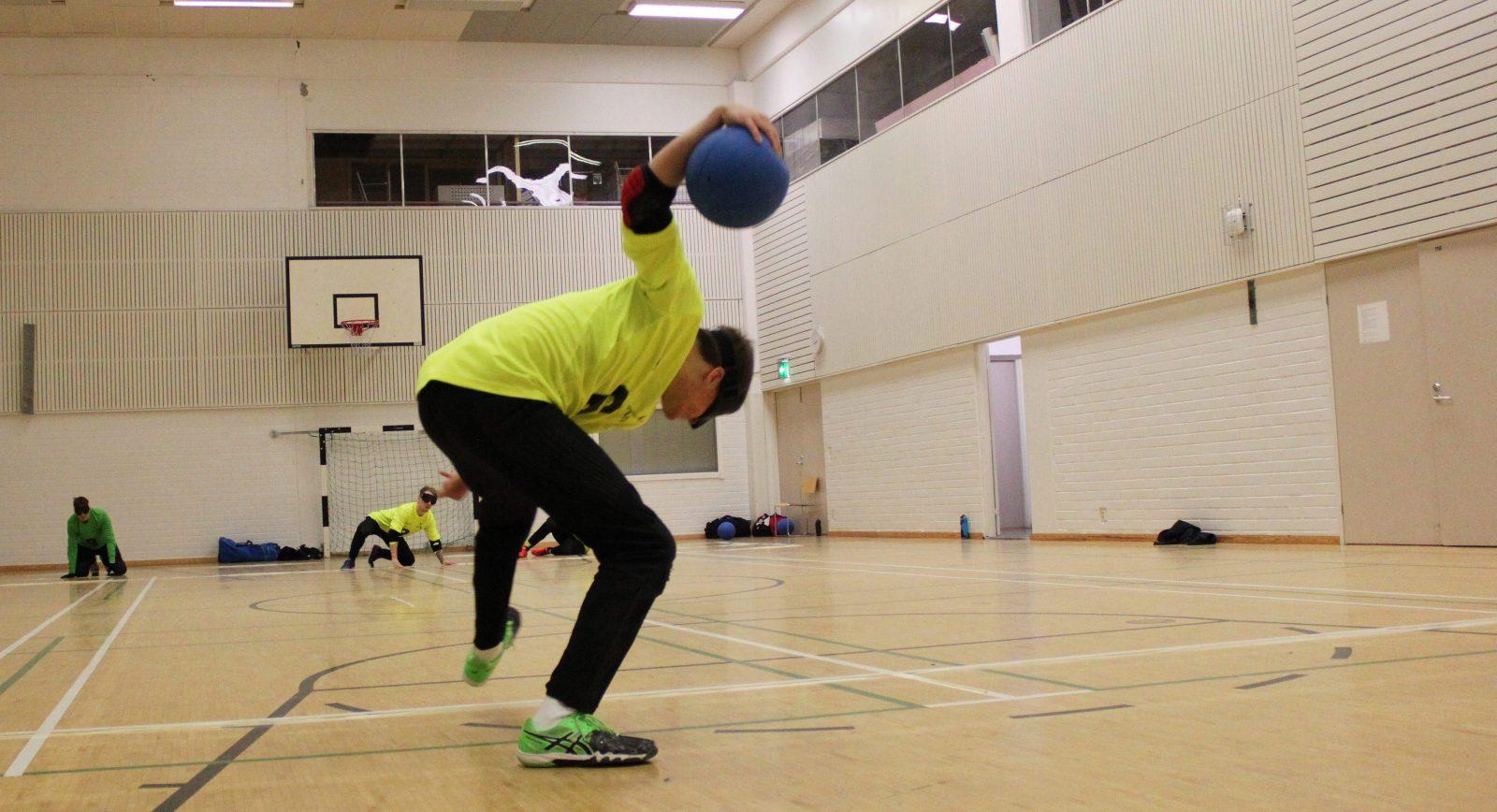 Aisti Sportin pelaaja pyörähtää heittoon. Vastapuolen Aistin pelaajat valmiudessa torjumaan.