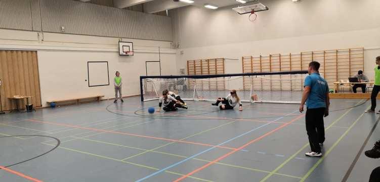 Pelitilannekuva, jossa O.P. Flying Ducks -joukkueen naispelaajat heittäytyvät puolustusasentoon