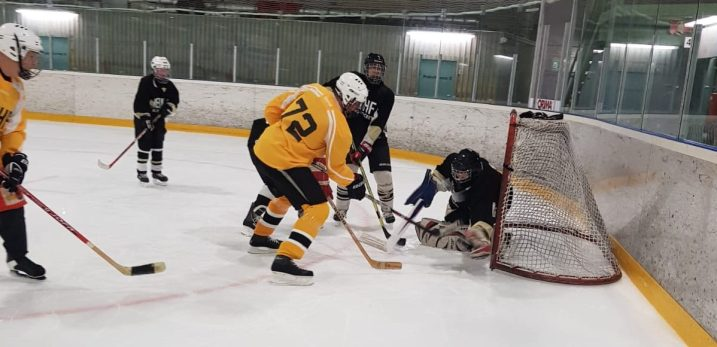 Pelitilannekuva näkövammaiskiekon hyökkäystilanteesta, jossa pelaajat yrittävät lyödä kiekkoa maaliin maalivahdin kurottaessa torjuntaan.