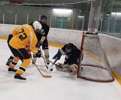 Pelitilannekuva hyökkäystilanteesta, jossa pelaajat yrittävät lyödä kiekkoa maaliin maalivahdin kurottaessa torjuntaan.