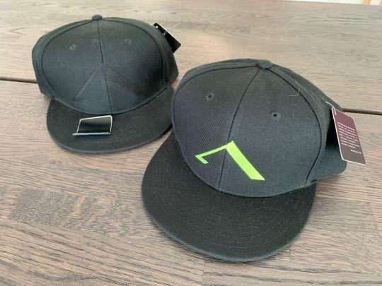 Musta Aisti Cap: kaksi mustaa cap-mallista lippistä joissa otsassa toisessa musta a-logo ja toisessa fluminon värinen a-logo.