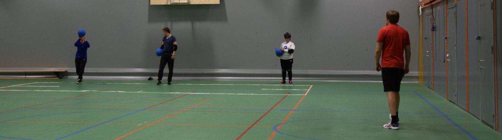Harjoituskuva jossa pelaajat maaliviivalla rivissä vasemmalta oikealle Eemi, Leo, Azra. Jokaisella pallo kourassa. Kentän laidalla Markus valmentamassa heittäjiä.