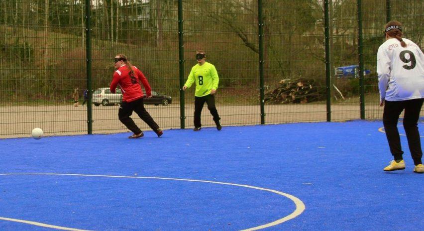 Pelitilannekuva sinisenväripohjaiselta jalkapallokentältä, jossa punapaitainen pelaaja on juuri käännähtänyt juoksuun kohti palloa. Taustalla näkyy keltapaitainen pelaaja ja etualalla valkopaitaisen numeron 9 pelaajan selkä. Pelaajilla on mustat lasit silmillään.