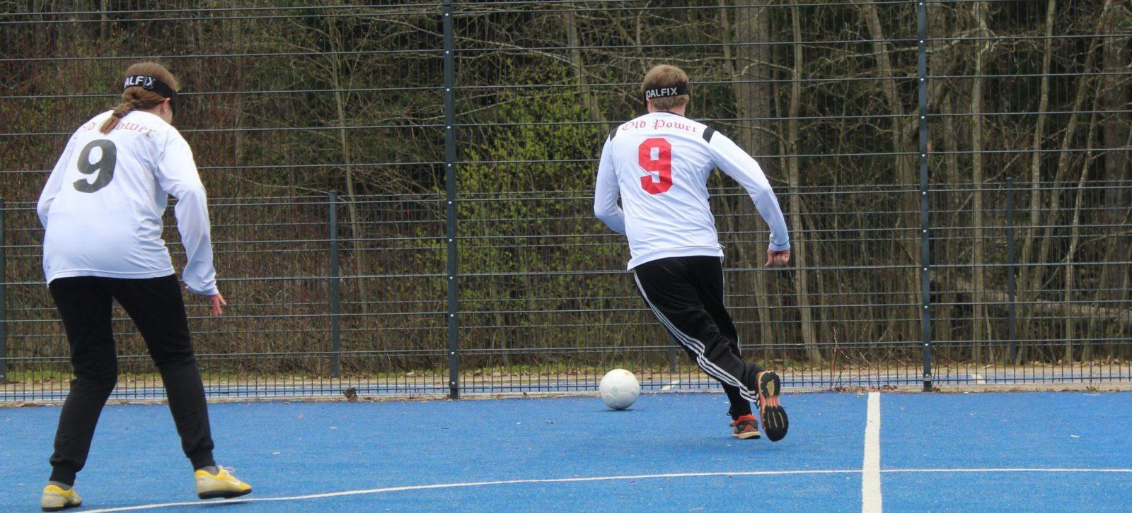 Pelitilannekuva jossa valkopaitainen mies juoksee laitaan potkaistun pallon perässä. Etualalla valkopaitainen nainen seisoo keskikentällä valmiudessa.