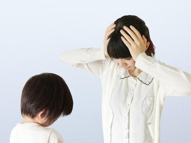 子どもを前にして頭を抱える女性